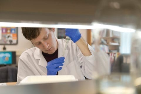 Male student with blue gloves uses pipette.