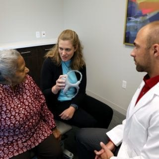 Assistant Professor Michelle Brown, P.T., D.P.T., a specialist in vestibular rehabilitation, utilizes a fluid-filled vestibular apparatus model to explain the inner ear and fluid dynamics of the semicircular canals to a patient in the physical therapy clinic Thursday, July 25, 2019. (DMU photo by Brett T. Roseman)